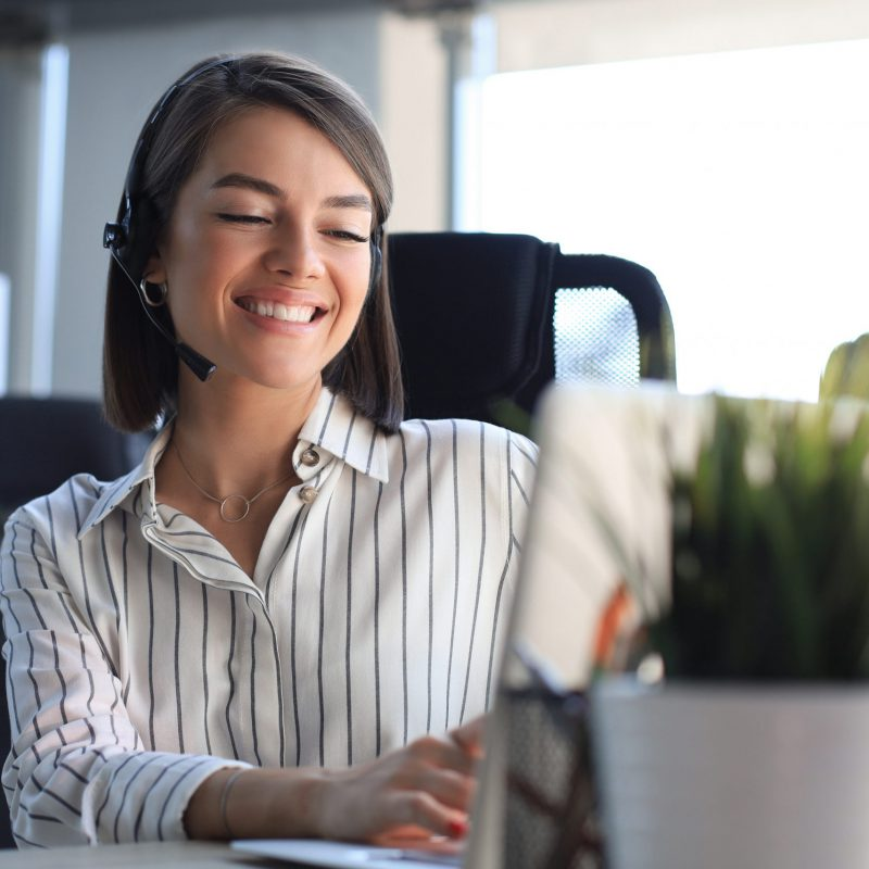 Beautiful,Smiling,Call,Center,Worker,In,Headphones,Is,Working,At